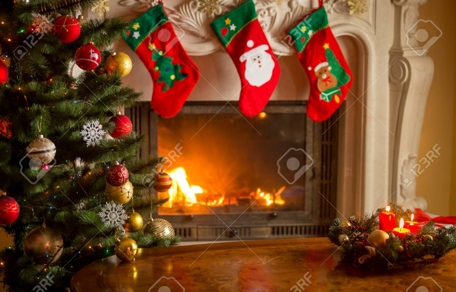 Empty wooden table in front of decorated fireplace and Christmas tree. Place for text.